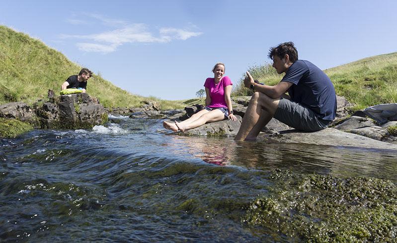 3 people bathing their feet in a stream